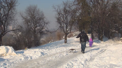 Family with Child and Sledge Walking in Park in Snow, Sledging in Winter Season Stock Footage