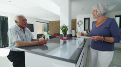 Happy retired couple enjoy hot drinks and cookies in their modern kitchen Stock Footage