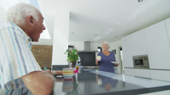 Happy retired couple enjoy hot drinks and cookies in their modern kitchen - stock footage