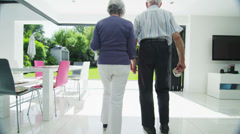Romantic senior couple hold hands & look out at the garden of their modern home Stock Footage