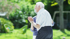 Romantic senior couple dancing together outdoors on a summer day Stock Footage