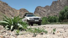 Jeep drive by, desert, arid landscape, mountains, Tajikistan - stock footage