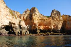 Caves in the cliffs yellow in lagos in the algarve portugal Stock Photos
