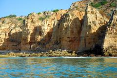 caves in the cliffs yellow in lagos in the algarve portugal - stock photo