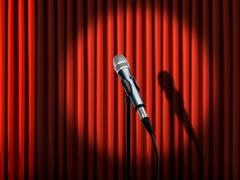 microphone under spotlight over red curtains - stock illustration