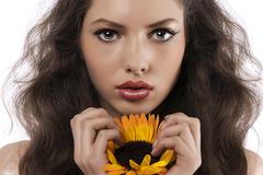 Natural girl with long hair holding a sunflower Stock Photos