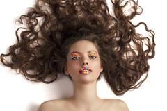 Beautiful model laying on white wearing candy make up Stock Photos