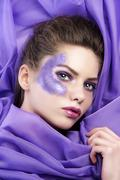young girl laying on purple fabric wearing glitter make up - stock photo