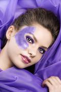 Stock Photo of laying model on purple fabric