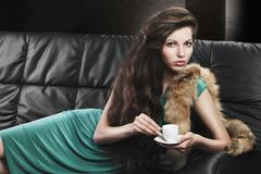 Young elegant girl in green with cup, she looks  in to the lens Stock Photos