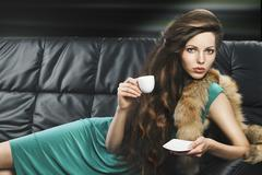 Young elegant girl in green with cup, she is lying on the sofa Stock Photos