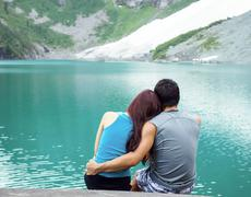 Young adults lovers looking at pristine aqua mountain lake Stock Photos