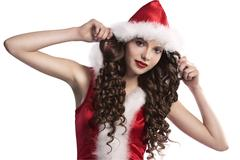 curly brunette dressed as santa claus - stock photo