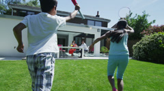 Happy asian family drinking cold drinks outside modern home on a summer day Stock Footage