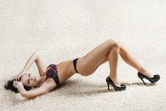 brunette in black underwear over a carpet, she looks in to the lens - stock photo