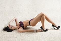 Stock Photo of brunette in black underwear over a carpet, she touches the heel of the shoe
