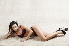 Brunette in black underwear over a carpet with sensual expression Stock Photos