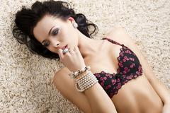 Girl in fashion lingerie on carpet with finger near the mouth Stock Photos