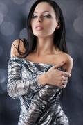 Sensual brunette with fashion silver dress in sensal position Stock Photos