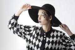 The letter on the face creative makeup girl, she takes the edges of the hat Stock Photos