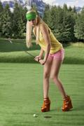 sexy golf player woman, she is hitting golf ball - stock photo
