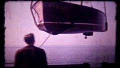 Classic wooden boat is lowered into water, 388  vintage film home movie Stock Footage