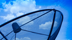 Time-lapse cloudy blue sky moving pass satellite signal wave receiver dish - stock footage