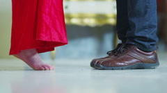 Woman in a red dress and her lover share a kiss. No faces can be seen Stock Footage