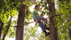 boy somersaults on the bar, and climbs a tree - stock footage
