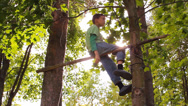 Stock Video Footage of boy somersaults on the bar, and climbs a tree