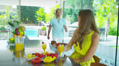 Happy young couple drinking healthy juice drinks in kitchen of modern home - stock footage