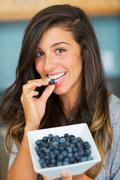 beautiful woman eating blueberries - stock photo