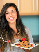 Woman eating waffles with fresh fruit Stock Photos