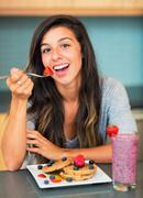 nainen syö vohveleita tuoreita hedelmiä - stock photo