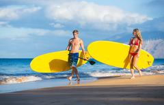 couple with stand up paddle boards - stock photo