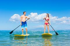 Couple stand up paddling in hawaii Stock Photos