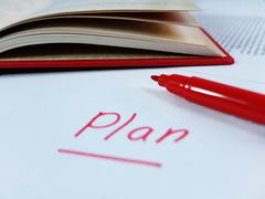 Handwritten Word Plan with Red Marker and Open Red Book - stock photo