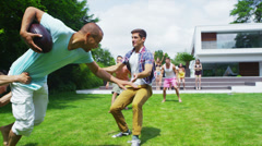 Athletic group of male friends play football in the garden of contemporary home Stock Footage
