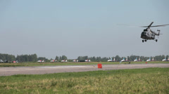A helicopter flies over the airfield at low altitude - stock footage