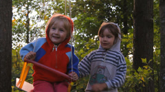 Two girls playing, laughing on a swing Stock Footage