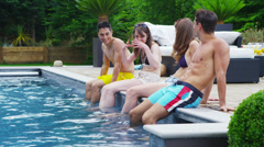 Attractive mixed ethnicity group of friends enjoying summer pool party Stock Footage