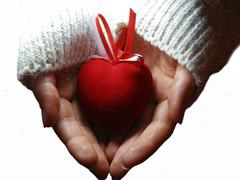 red heart with red and white stripes on woman hands - stock photo