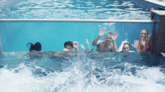 Attractive friends enjoying pool party in modern pool with clear glass panel Stock Footage