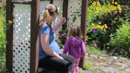 Stock Video Footage of Pregnant Mother and Daughter in Flower Garden