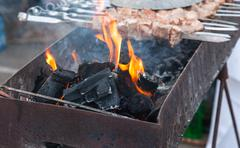 traditional preparation of a shish kebab on fire closeup - stock photo