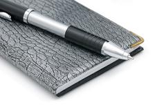 a pen and notebook - stock photo