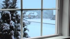 Snowing at dusk in a residential area seen through window Stock Footage