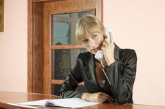 blond receptionist at phone - stock photo