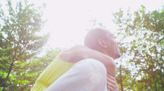 Happy couple outdoors on a summer day with sunlight streaming through the trees Stock Footage