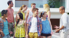 Portrait of happy group of young friends standing outside contemporary home Stock Footage